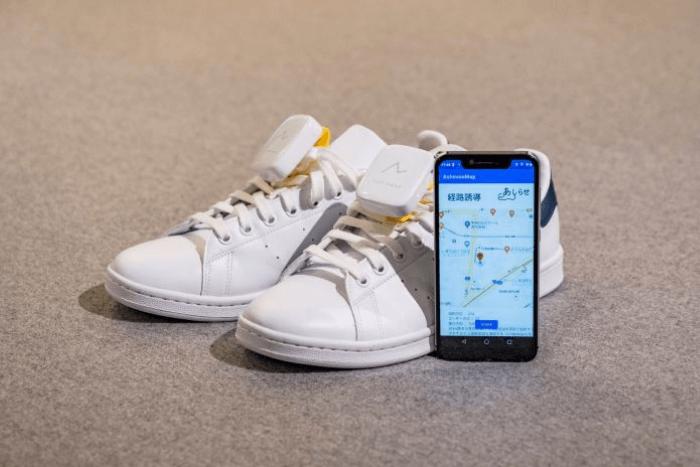Ένα ζευγάρι παπούτσια με το σύστημα πλοήγησης και δίπλα ένα smartophone