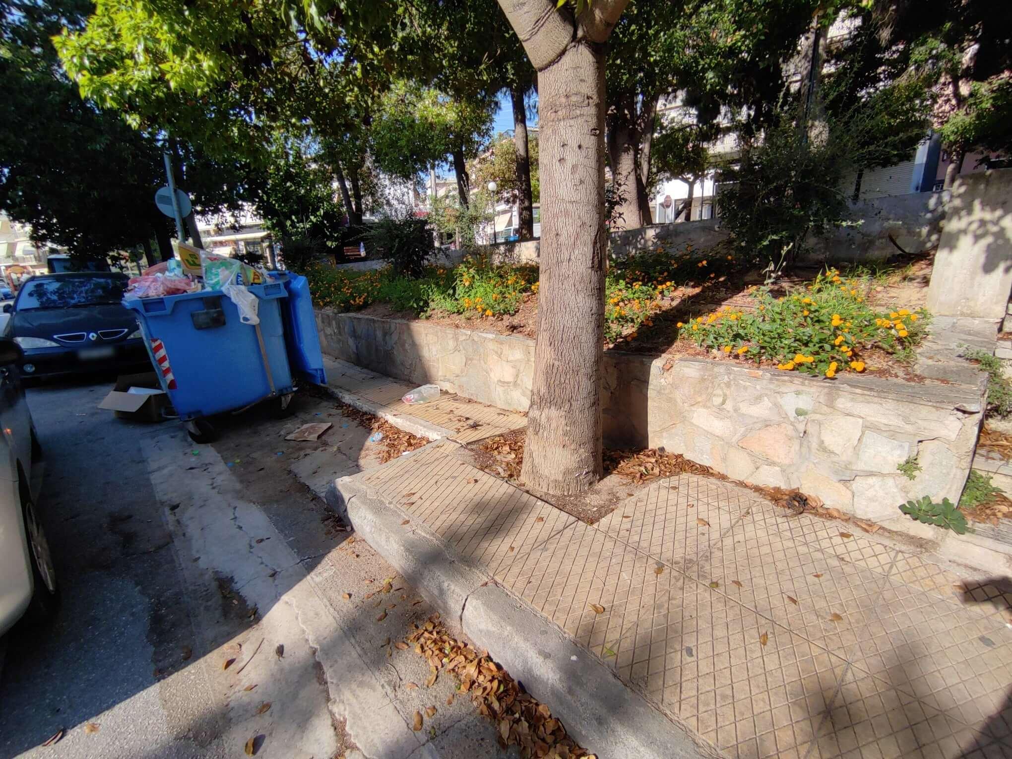 Πολυτέκνων - Πάρκο. Το πλάτος του πεζοδρομίου περιορίζεται σημαντικά από την εσοχή για τον κάδο ανακύκλωσης. Ταυτόχρονα, το δέντρο που υπάρχει επί του πεζοδρομίου δεν αφήνει επαρκή χώρο για τους πεζούς.