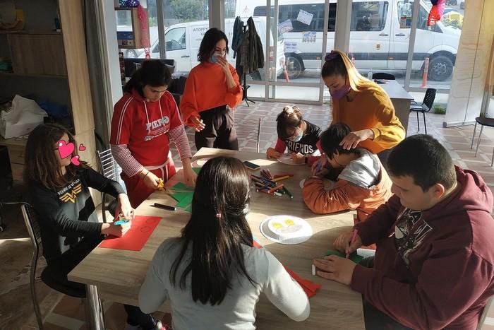 Φωτό από την έναρξη λειτουργίας του Κοινωνικού Στεκιού ΑμεΑ. 6 παιδιά κάθονται σε ένα μεγάλο τραπέζι και δημιουργούν με μαρκαδόρους και χαρτιά. Από πάνω τους 2 κοπέλες-ειδικοί δημιουργικής απασχόλησης τα συντονίζουν.
