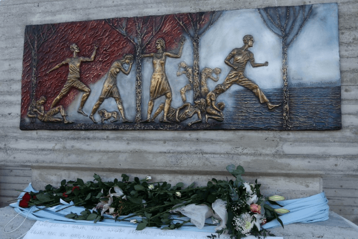 Ακουμπισμένα λουλούδια στο μνημείο στο Μάτι. το μνημείο είναι ανάγλυφο και απεικονίζει ανθρώπους που τρέχουν να ξεφύγουν από την φωτιά ανάμεσα από το δάσος και να φτάσουν στη θάλασσα. Κάποιοι άνθρωποι και ζώα είναι ήδη πεσμένοι/νεκροί. Οι άνθρωποι απεικονίζονται με χρυσό χρώμα, η φωτιά με κόκκινο και η θάλασσα με γκρι.