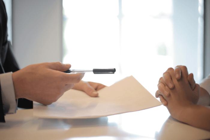 εργοδότης με χαρτιά και στυλό ετοιμάζεται να δώσει σε εργαζόμενο να υπογράψει (φαίνονται μόνο χέρια)