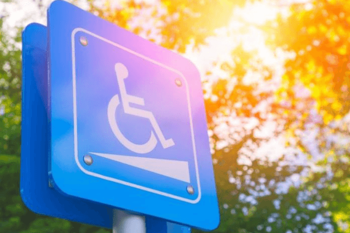 Αναπηρικό σήμα σε ταμπέλα πίσω φαίνονται δέντρα
