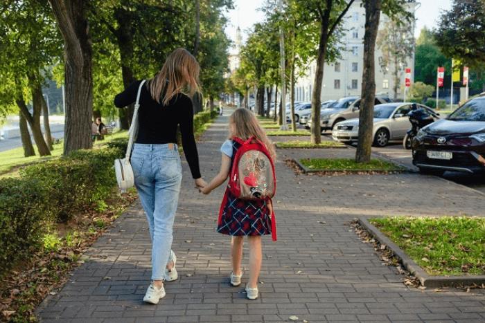 παιδί με σχολική τσάντα κρατάει από το χέρι τη μητέρα του και περπατάνε