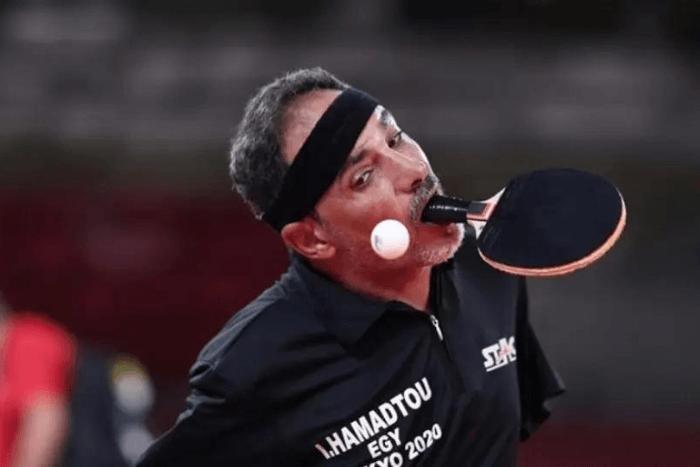 Ο Ιμπραχίμ Χαμαντού με ρακέτα στο στόμα παίζοντας πινγκ πονκ