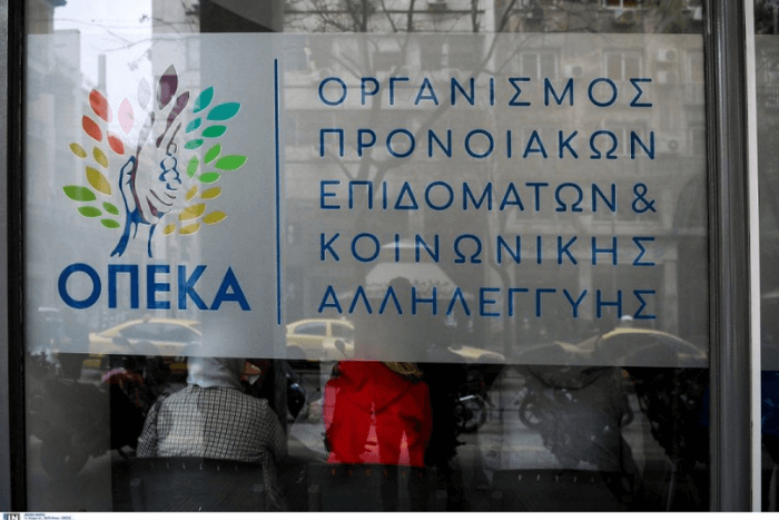 Τζαμαρία με λογότυπο ΟΠΕΚΑ και από πίσω άτομα που κάθονται (πλάτη) σε δημόσιο οργανισμό