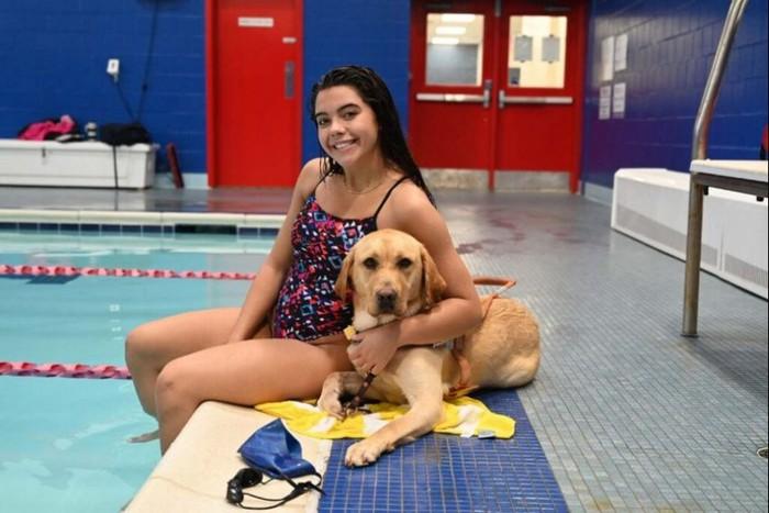 Η Anastasia Pagonis καθισμένη στην πισίνα αγκαλιά με τον σκύλο οδηγό της