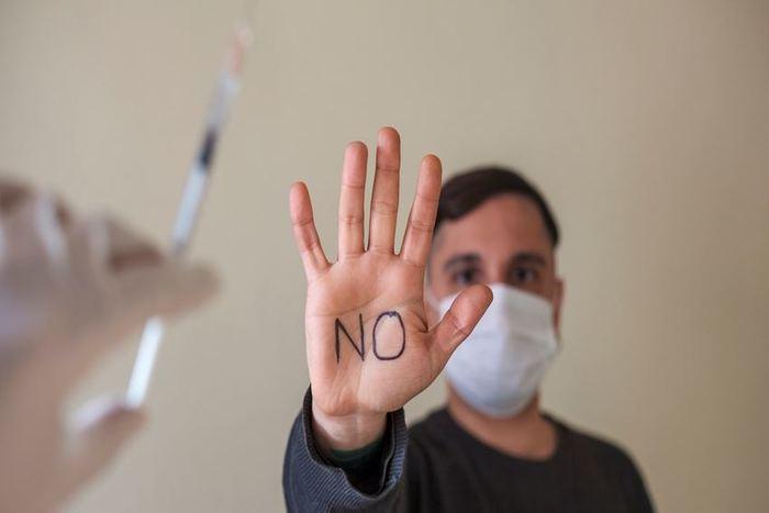 ένα χέρι που κρατάει ένα εμβόλιο. Μπροστά του ένας άντρας με μάσκα που υψώνει την παλάμη του στην οποία είναι γραμμένη η λέξη όχι στα αγγλικά.