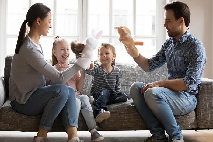 2 γονείς παίζουν με τα 2 παιδιά τους σε έναν καναπέ, φορώντας κούκλες κουκλοθέατρου στα χέρια