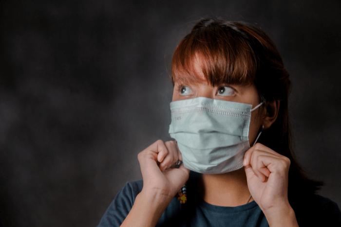 Κορίτσι στην εφηβεία φοράει χειρουργική μάσκα και κοιτάει με φόβο προς τα πάνω