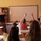 μαθητές με σηκωμένα χέρια σε σχολική τάξη, στο βάθος η δασκάλα τους