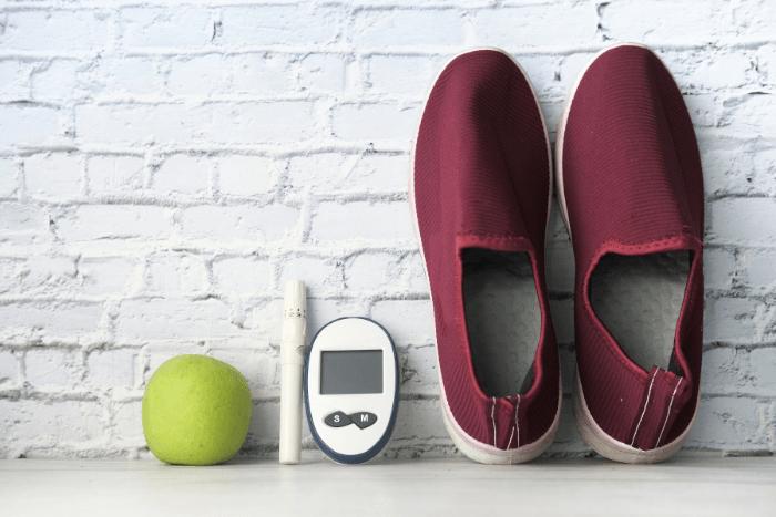 ένα ζευγάρι παπούτσια, ένας μετρητής σακχάρο, ένα στυλό ινσουλίνης και ένα πράσινο μήλο.