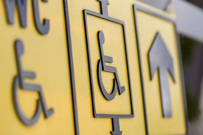 κοντινή φωτογραφία από το διεθνές σήμα του αναπηρικού αμαξιδίου, σε μαύρο χρώμα με κίτρινο φόντο
