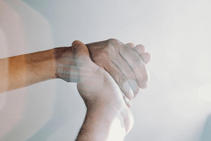 Χέρια δύο αντρών κρατιούνται
