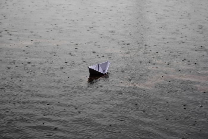 Χάρτινο καραβάκι που πλέει σε νερά εν μέσω βροχής