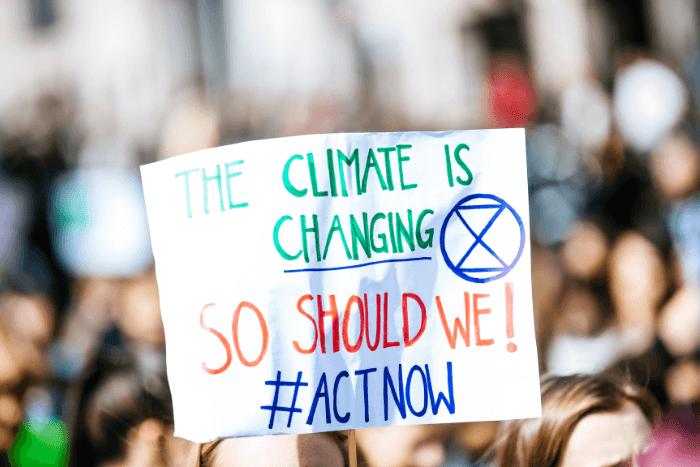 """Πλακάτ σε διαδήλωση που αναγράφει """"The climate is change! So should we #ACTNOW"""""""
