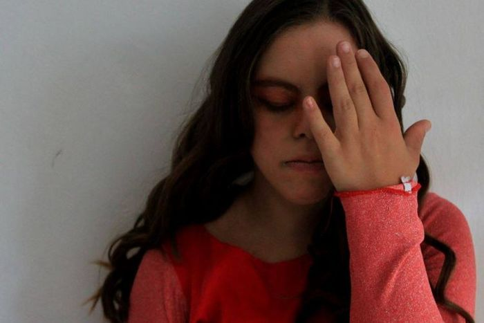 Η Λωξάντρα Λούκας με κοραλλί μπλούζα ακουμπά το χέρι της μπροστά από το πρόσωπό της.