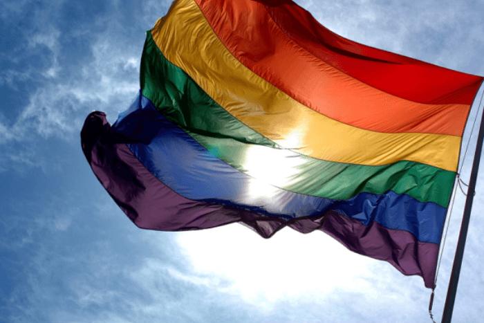 Σημαία ΛΟΑΤΚΙ κοινότητας ανεμίζει με φόντο τον ουρανό
