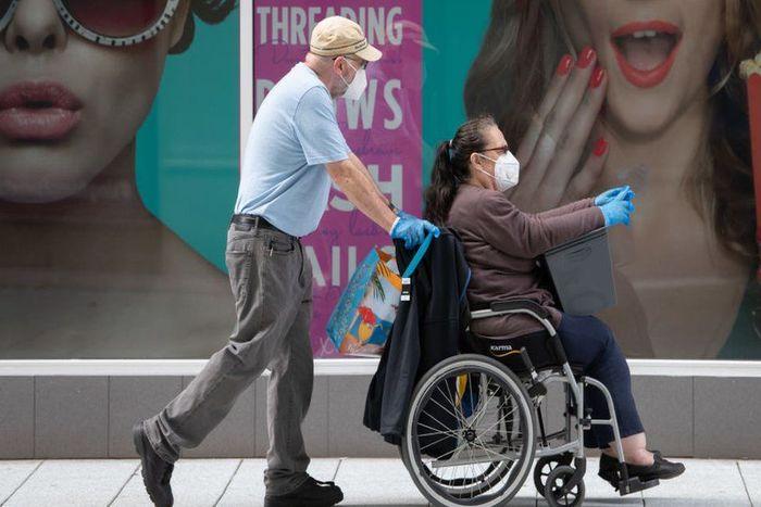 άντρας βοηθά στη μεταφορά της ανάπηρη γυναίκα σε αμαξίδιο