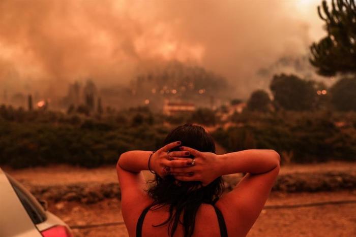 κοπέλα γυρισμένη πλάτη με τα χέρια σταυρωμένα πίσω από το κεφάλι της κοιτάζει μια τεράστια φωτιά που απλώνεται στο βάθος μπροστά της
