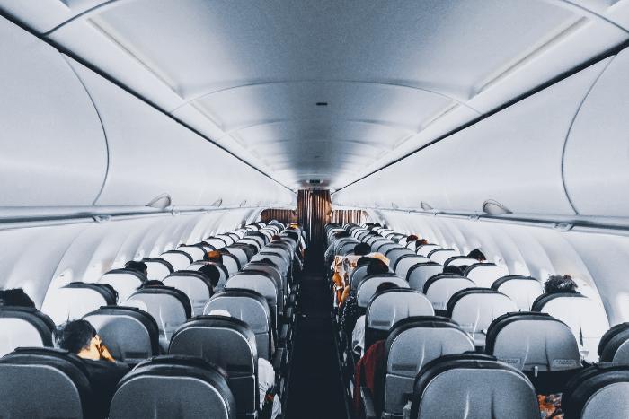 Εσωτερικό αεροπλάνου. Κάποιοι επιβάτες κάθονται στη θέση τους.