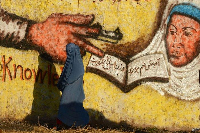 μια γυναίκα με μπούργκα περνάει μπροστά από ένα γκράφιτι θρησκευτικού περιεχομένου