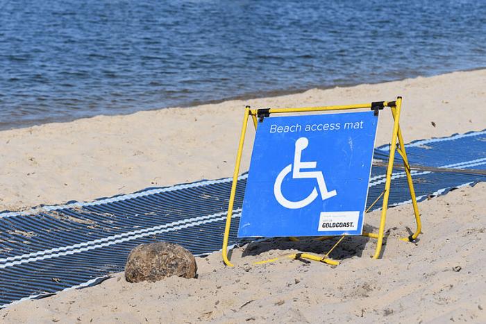 """Παραλία με ταμπέλα που έχει το σήμα του αναπηρικού αμαξιδίου και γράφει """"beach acces mat"""""""