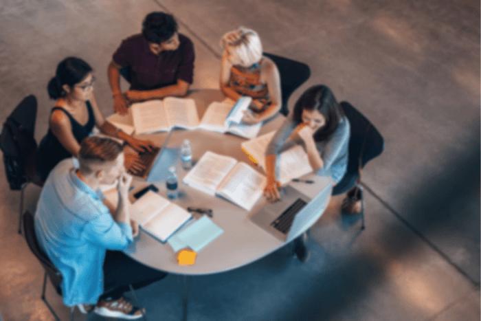 Στρογγυλό τραπέζι με 5 άτομα που έχουν μπροστά τους βιβλία και λάπτοπ