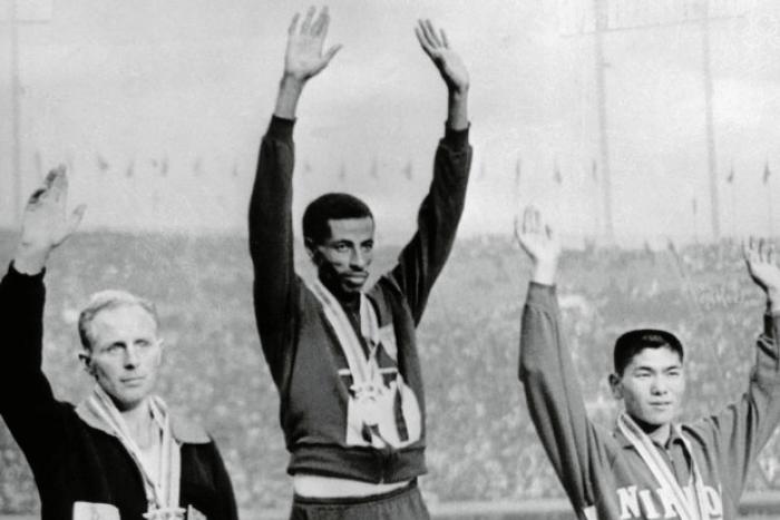 Ο Αμπέμπε Μπικίλα στο βάθρο παίρνοντας ο χρυσό μετάλλιο δίπλα του οι άλλοι δύο ολυμπιονίκες του χάλκινου και αργυρού μεταλλίου