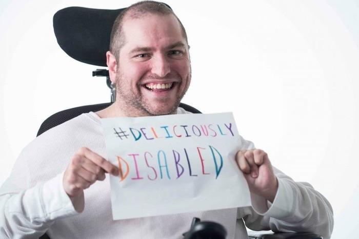 """ο Άντριου Γκούρζα καθισμένος στην αναπηρική καρέκλα του, κρατώντας ένα χαρτί πυο γράφει με πολύχρωμα γράμματα στα αγγλικά """"λαχταριστά ανάπηρος"""""""