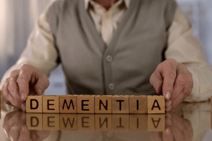 """Ηλικιωμένος από τον λαιμό και κάτω που κρατάει κύβους ξύλινους που σχηματίζουν τη λέξη """"Dementia""""=Άνοια"""