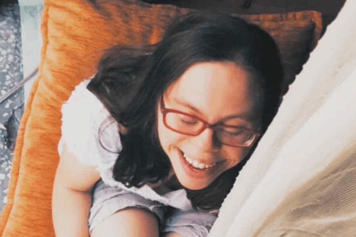 Η Λωξάντρα Λούκας καθισμένη σε καναπέ χαμογελαστή και με κλειστά μάτια)