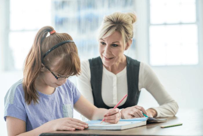 Κορίτσι με γυαλιά οράσεως γράφει σε βιβλίο και δίπλα η μητέρα του παιδιού.
