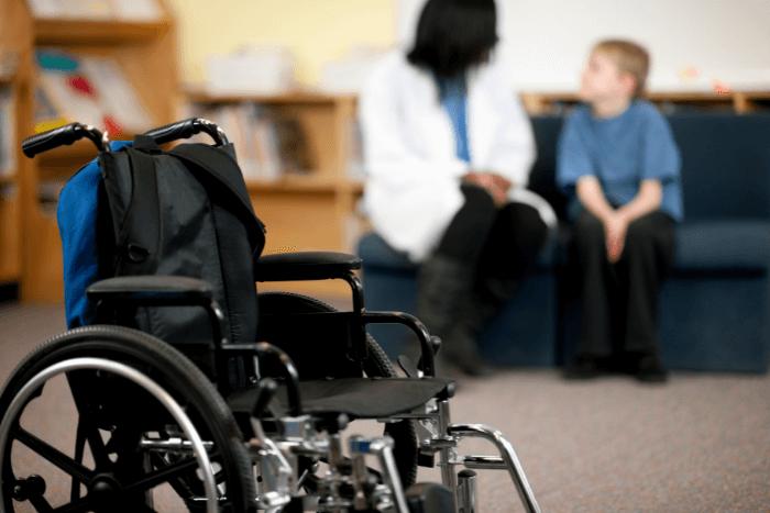 Σε πρώτο πλάνο αναπηρικό αμαξίδιο και πίσω παιδί με αναπηρία που συζητάει με γιατρό