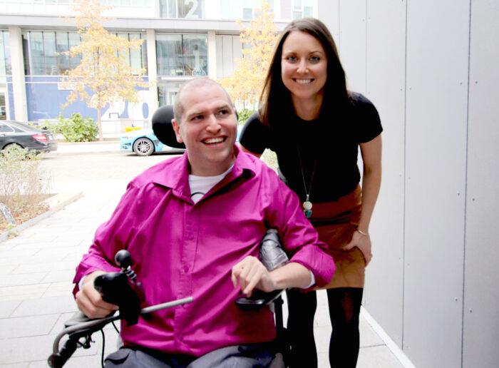 Ο Andrew Gurza και η Heather Morrison. Ο Gurza κάθεται στο αμαξίδιό του χαμογελαστός, φορώντας ένα φούξια πουκάμισο. Η Morrison από πάνω του με μαύρο μπλουζάκι ελαφρώς σκυφτή και χαμογελαστή