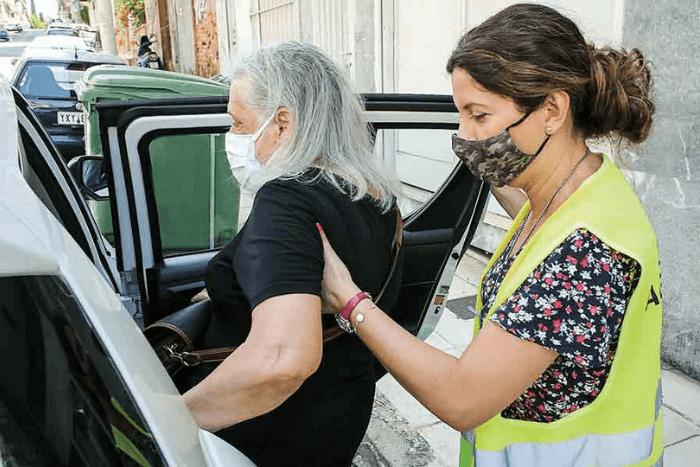 Η νοσηλεύτρια Βασιλική Τιακούδη βοηθάει τη Μαργαρίτα Δημητριάδου να μπει στο όχημα του «Βοήθεια στο Σπίτι», πριν τη συνοδεύσει στο νοσοκομείο.