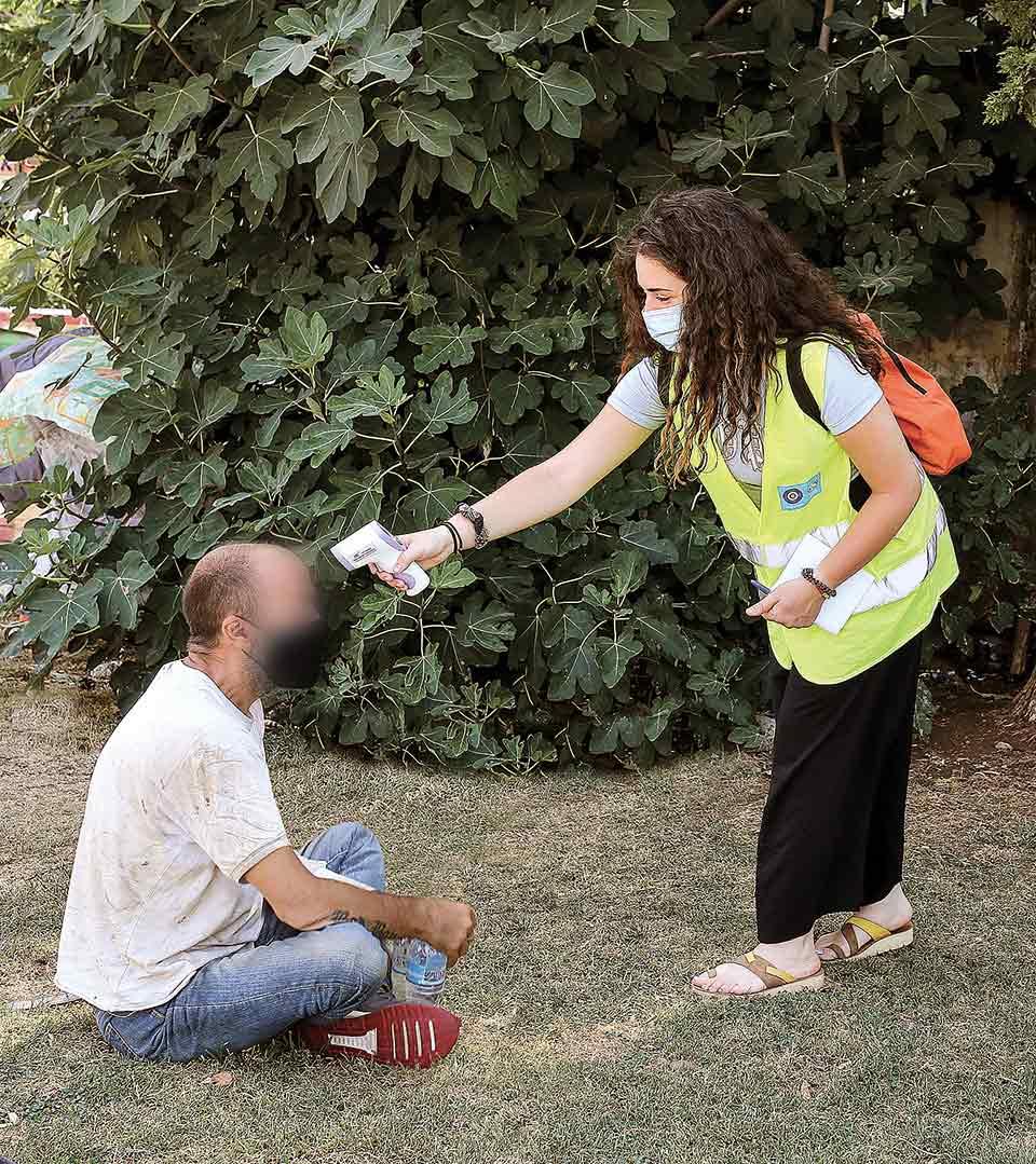 Κοινωνικές λειτουργοί και νοσηλεύτριες του προγράμματος «Streetwork» του Δήμου Αθηναίων θερμομετρούν και προσφέρουν νερό σε αστέγους στο κέντρο της Αθήνας.