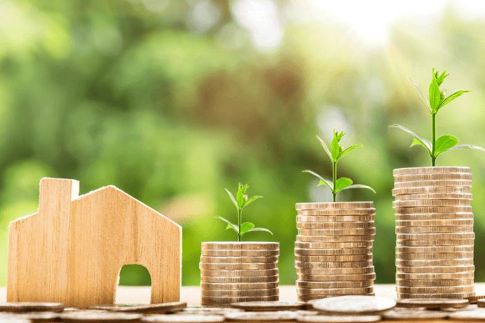 Μικρογραφία σπιτιού σε ξύλινη μικρή μακέτα και δίπλα τρεις στήλες σε κέρματα που από πάνω τους υπάρχουν πράσινα φυλλαράκια .