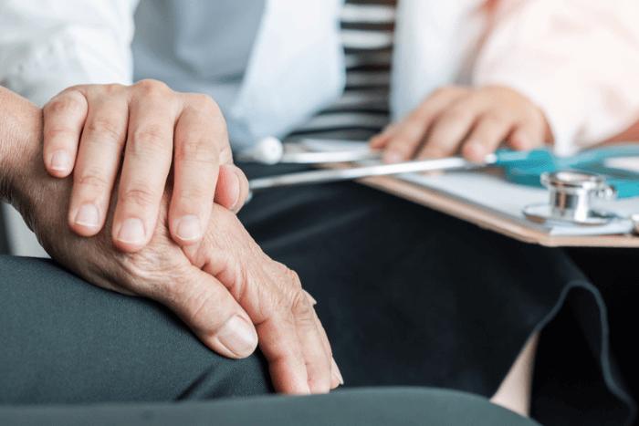 Γιατρός που αγγίζει το χέρι ασθενούς τρίτης ηλικίας (φωτογραφία κοντινό στα χέρια)