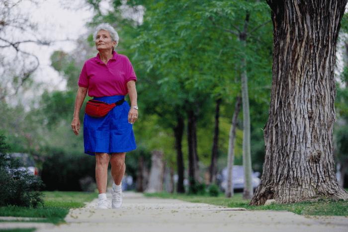 Ηλικιωμένη γυναίκα που περπατάει σε πάρκο