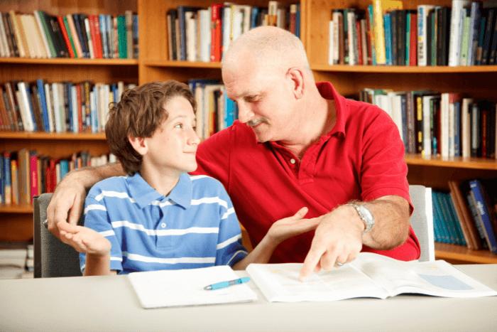 Μαθητής με βιβλία μπροστά του και δίπλα του εκπαιδευτικός παράλληλης στήριξης