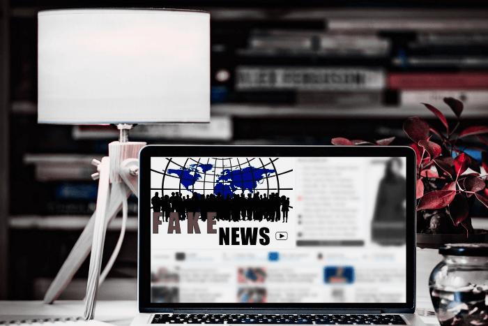 """Λάπτοπ πάνω σε γραφείο που στην οθόνη του αναγράφει τη φράση """"fake news"""". Αριστερά ένα πορτατιφ και δεξιά ένα βάζο με λουλούδια."""