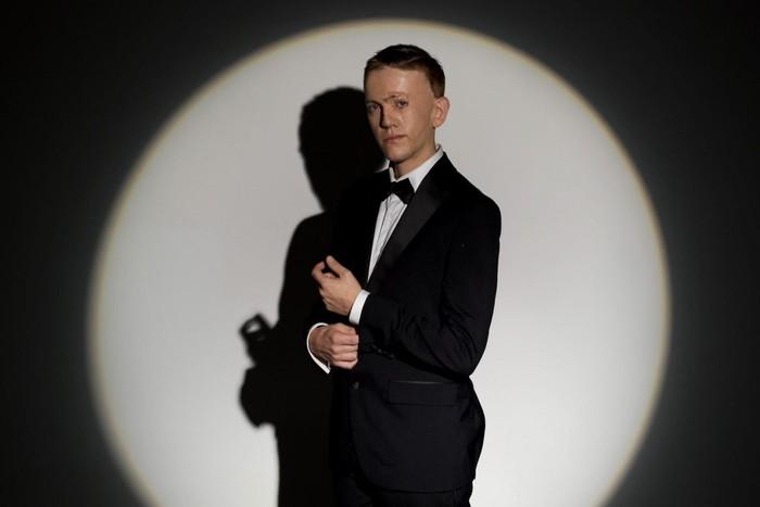 νεαρός άντρας με ελαφρώς παραμορφωμένη όψη στον ρόλο του Τζέιμς Μποντ. Φοράει μαύρο κουστούμι και παπιγιόν και το φως ενός προβολέα πέφτει πάνω του δημιουργώντας σκιά.