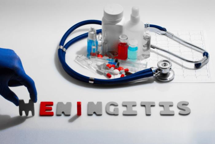 """Ένα χέρι σχηματίζει τη λέξη """"Meningitis"""" με ανάγλυφα γράμματα και από πάνω υπάρχουν φάρμακα, εμβόλια κι ένα στηθοσκόπιο"""