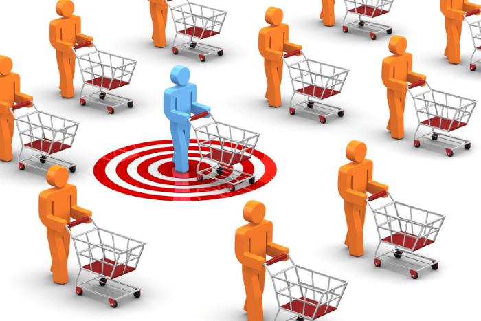 Πορτοκαλί ανθρωπάκια που έχουν μπροστά τους καροτσάκια του σούπερ μάρκετ και στη μέση ένα ανθρωπάκι μπλε μέσα σε ένα κόκκινο κύκλο που και αυτό έχει μπροστά του καρότσι του σούπερ μάρκετ