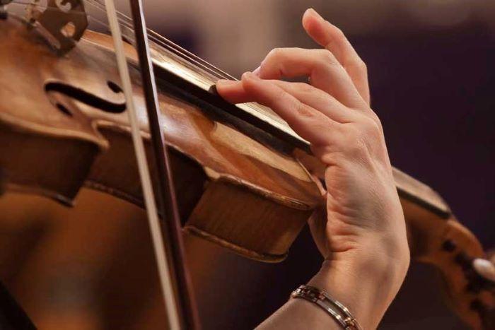 χέρι βιολιστή ή βιολίστριας πάνω σε βιολί εν ώρα οργανοπαιξίματος