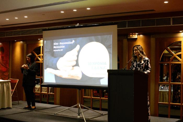 Η Μανουέλλα Καγιοπούλου μιλώντας στην εκδήλωση για τα 30 χρόνια ΣΔΕΝ, δίπλα της διερμηνέας ελληνικής νοηματικής γλώσσας