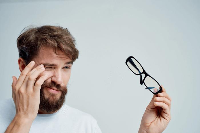 άνδρας που κρατάει στο χέρι ένα ζευγάρι γυαλιά οράσεως και με το ένα μάτι κλειστό δοκιμάζει αν βλέπει