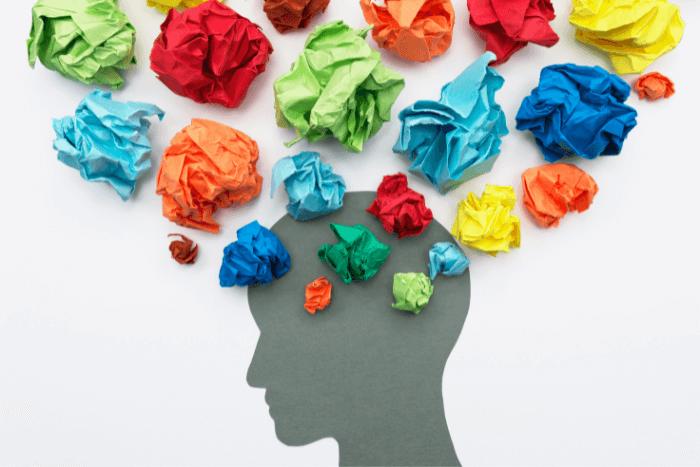 Σκίτσο ενός κεφαλιού και πάνω στον εγκέφαλο υπάρχουν στρογγυλά χρωματιστά χαρτάκια