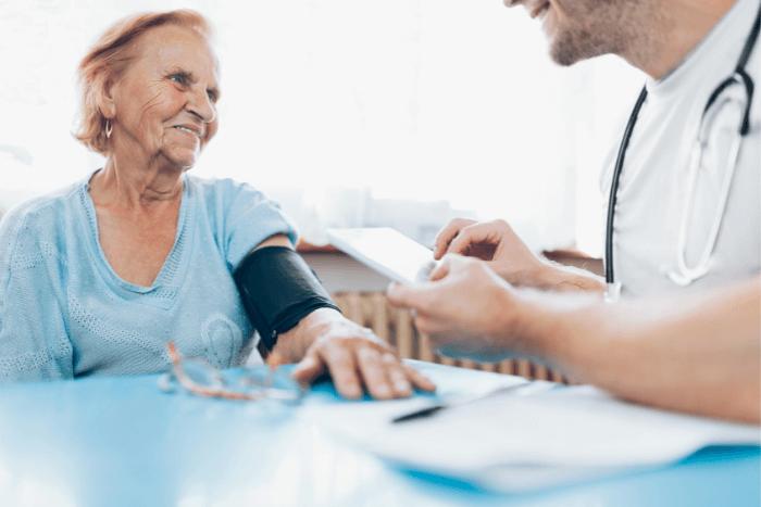 Ιατρός παίρνει την πίεση σε ηλικιωμένη γυναίκα και κρατάει σημειώσεις