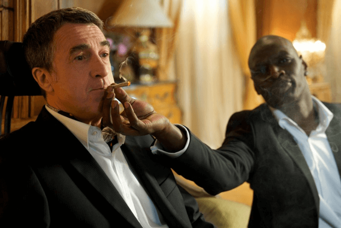 Από τη ταινία Άθικτοι: ο μαύρος βοηθός να κρατάει το τσιγάρο στο στόμα του τετραπληγικού εργοδότη του